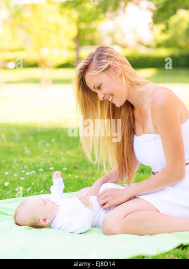 happy mother lying with little baby on blanket - Stock Image
