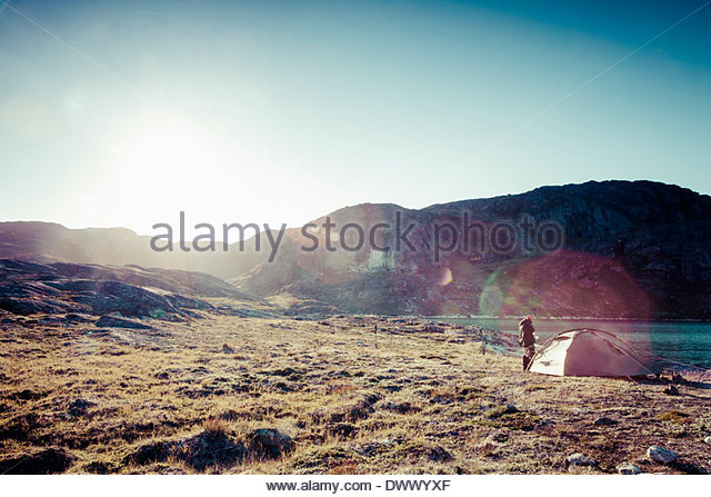 Person near tent at campsite with mountains in background - Stock Image