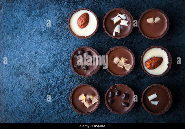 Composition of chocolate candies on a blue stone horizontal - Stock Image