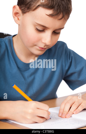 Schoolboy doing his homework at his desk - Stock Image