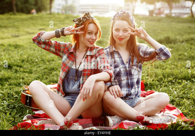 Two Young Smiling Hipster Girls Having Fun at a Picnic in the Park in the Sunset - Stock Image