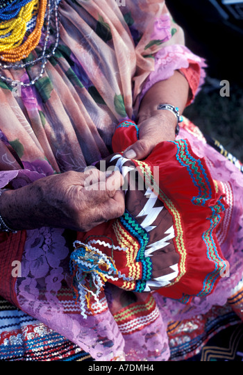 Florida Seminole Indian woman sewing bright colors - Stock Image