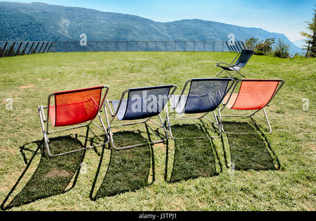 Five deck chairs on the terrace with panoramic mountain views - Stock Image