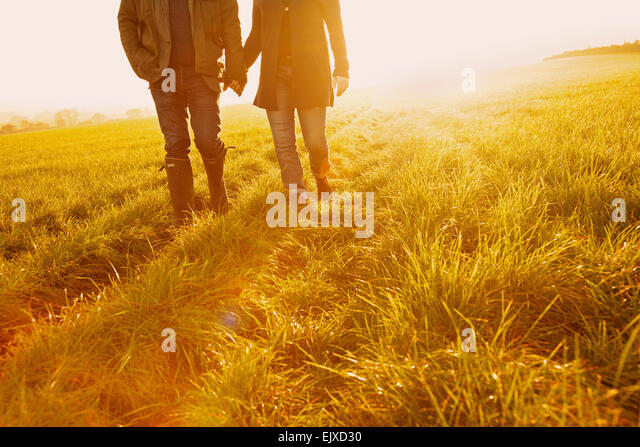 Couple Walking in a Field Holding Hands, Low Section - Stock Image