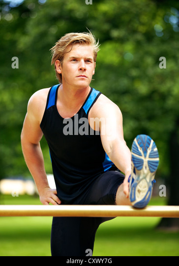 Athlete at the park looking serious while stretching his legs - Stock Image