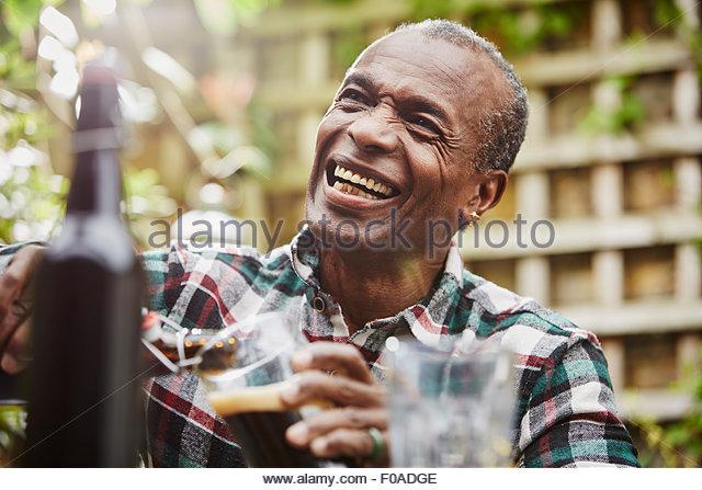 Senior man pouring beer, laughing - Stock Image