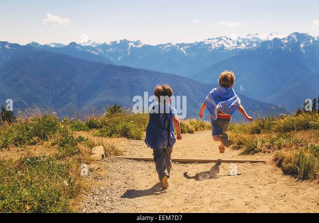 Two young boys (2-3, 4-5) wearing super hero capes running on mountain - Stock Image