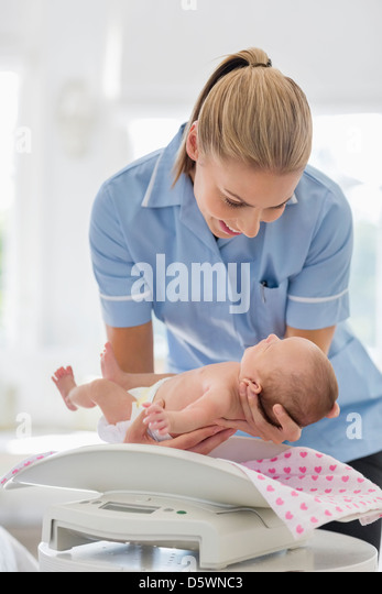 Nurse weighing newborn baby - Stock Image