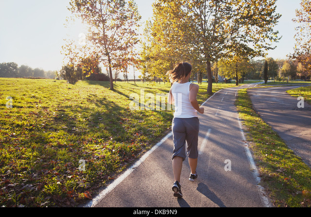 woman running in the park, fitness background - Stock Image