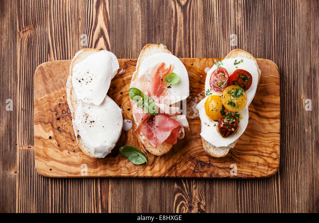 Three bruschettas with mozzarella cheese, ham and roasted tomatoes on ciabatta bread on wooden background - Stock Image
