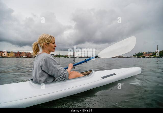 Woman kayaking on river - Stock-Bilder