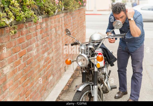 Mid adult man checking hair in motorbike side mirror - Stock Image