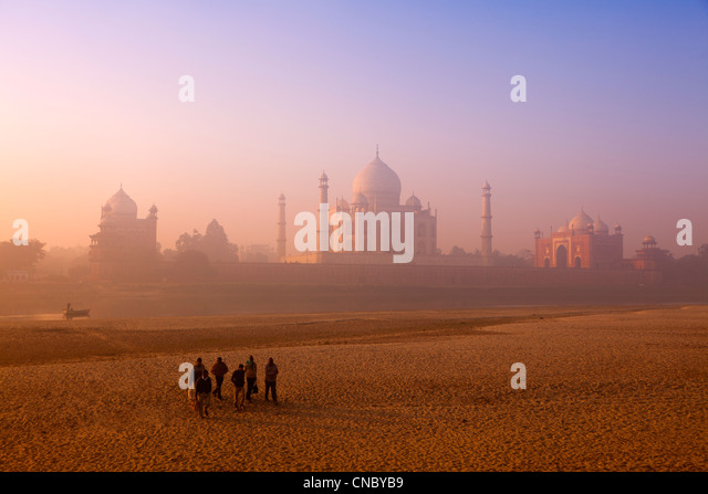 India, Uttar Pradesh, Agra, Taj Mahal workers crossing dried up Yamuna river at sunrise - Stock-Bilder