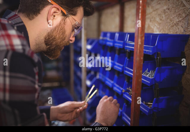 Carpenter selecting nails from shelf - Stock Image
