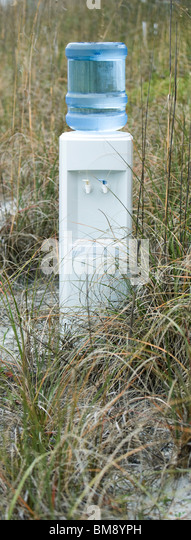 Water cooler in field of dry grass - Stock Image