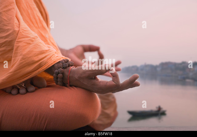 Holy man meditate on the river bank of the Ganges Varanasi India - Stock-Bilder