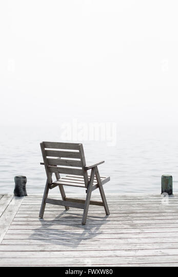 Sweden, Stockholm Archipelago, Grasko, Chair standing on jetty - Stock Image