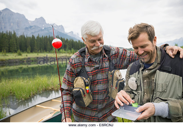 Father and son examining fishing tackle - Stock Image