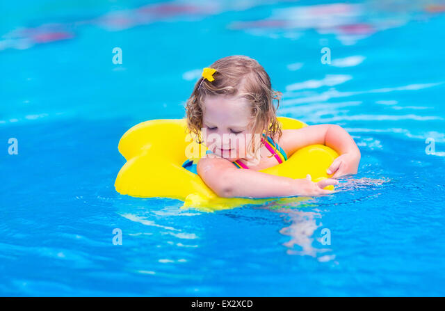 Kids in swimming pool. Children swim outdoors. Toddler child during vacation in a tropical resort with palm trees. - Stock Image