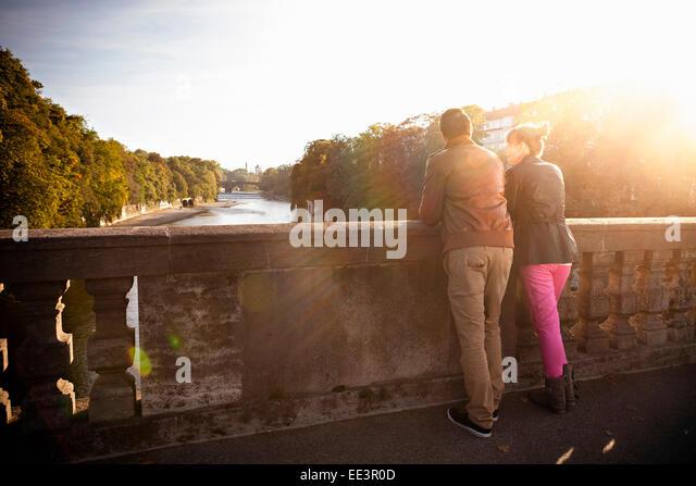 Young couple standing on Luitpoldbrücke, Munich, Bavaria, Germany - Stock-Bilder