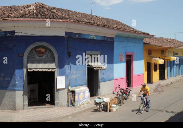 Nicaragua Granada Calle Vega colonial heritage neighborhood street scene corner building business colorful cyclist - Stock Image