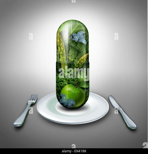 Food supplement concept as a giant pill or medicine capsule with fresh fruit and vegetables inside on a table place - Stock-Bilder
