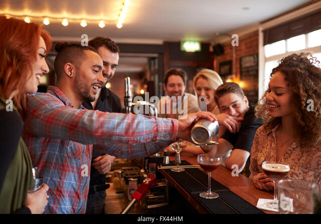 Man Learning How To Mix Cocktail At Lesson In Bar - Stock Image