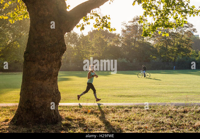 A runner runs with a late afternoon sun in a london park - Stock Image