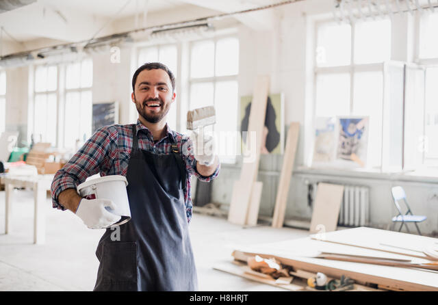 Happy young painter holding paint brush and showing it to camera - Stock Image