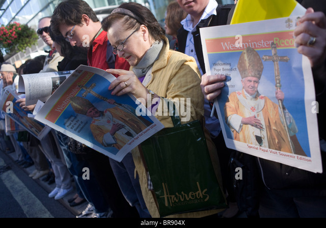 Catholics read free newspapers to crowds outside Westminster Cathedral before Pope Benedict XVI arrives. - Stock-Bilder