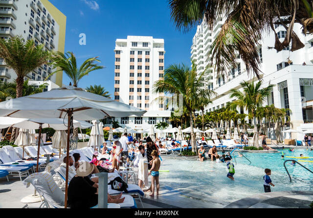 Miami Beach Florida Loews Miami Beach Hotel St. Moritz Hotel swimming pool wading children umbrellas palm trees - Stock Image