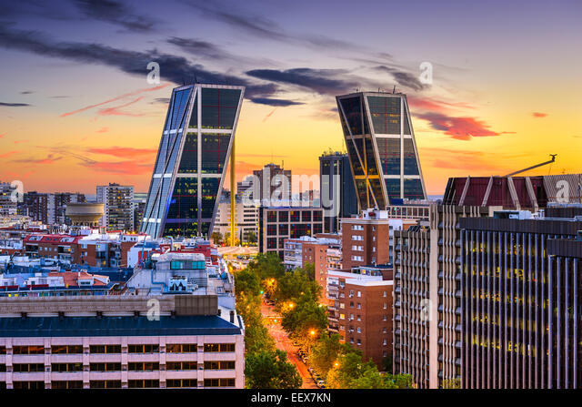 Madrid, Spain financial district skyline at twilight viewed towards the Gate of Europe Plaza. - Stock Image