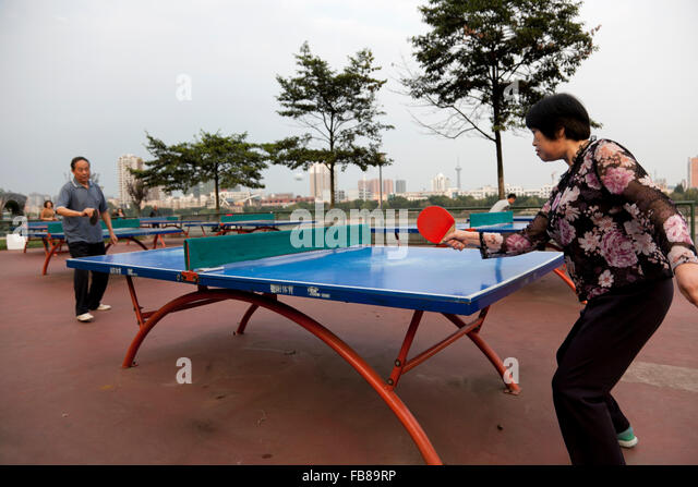 People play table tennis at a park on the riverfront at a typical city in China. - Stock Image