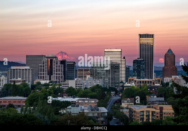 Skyline view of Portland, Oregon, USA with Mt Hood and the rising moon seen in the distance - Stock-Bilder