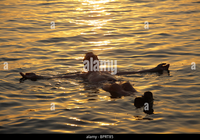 Man floating in the dead sea at sunset, Jordan - Stock Image