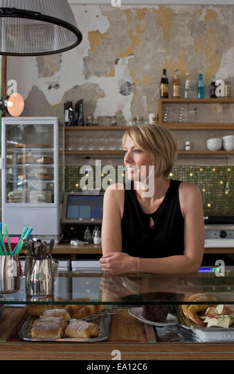 Mid adult woman working in cafe - Stock Image