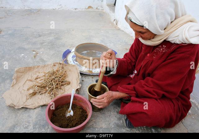 Woman grinding spices, Douz, Kebili, Tunisia, Africa - Stock Image