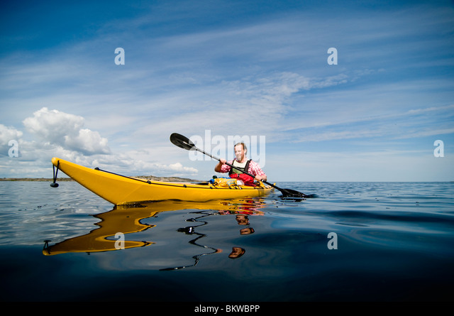 Man in yellow canoe - Stock Image