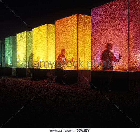 Silhouette of three people standing with colored cubes - Stock Image