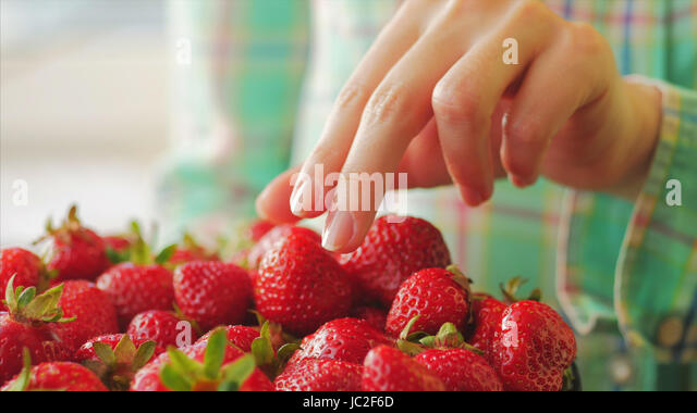 Young girl picks a delicious ripe strawberry from the black plate. Beautiful background. Lady chooses a berry. - Stock Image