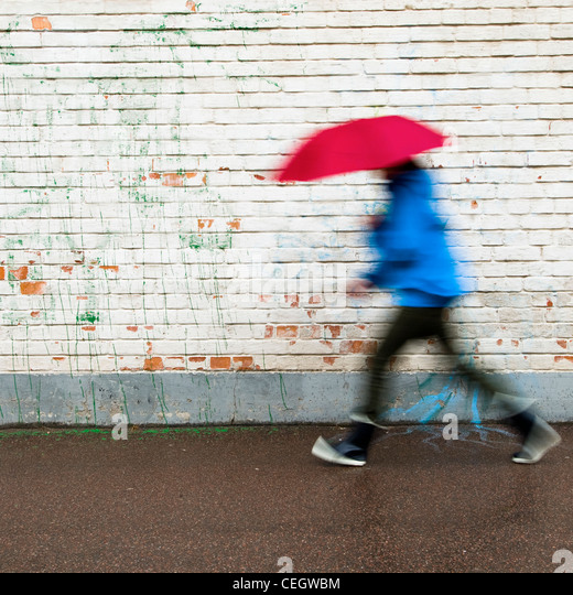 Person walking in rain with umbrella - Stock-Bilder