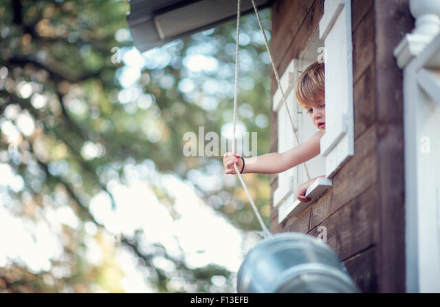 Toddler pulling a bucket up to his treehouse - Stock Image