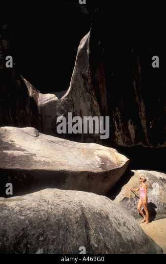 British Virgin Islands The Baths woman alone beside huge granite boulders Virgin Gorda caribbean islands - Stock Image