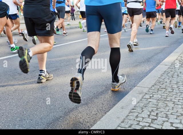 People running fast in a city marathon on street - Stock Image