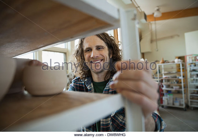 Pottery technician pushing shelf in pottery studio - Stock Image
