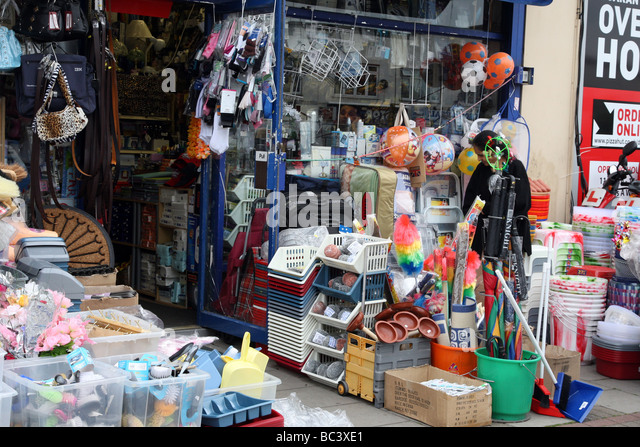 Pound shop on High Road, Kilburn, London, displaying cheap goods for sale on side of road. - Stock Image