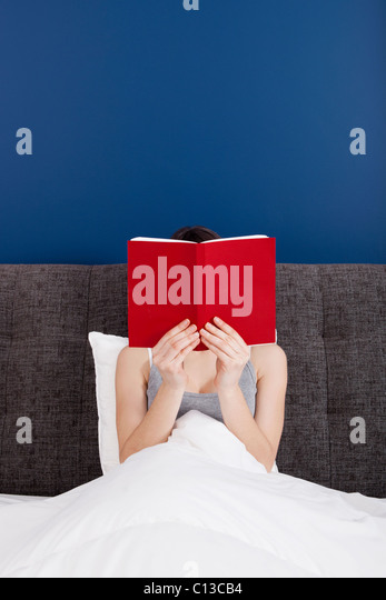 Woman reading a book with the face covered by the book - Stock Image
