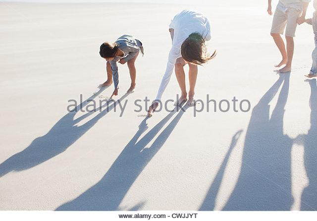 Family writing in sand on beach - Stock-Bilder