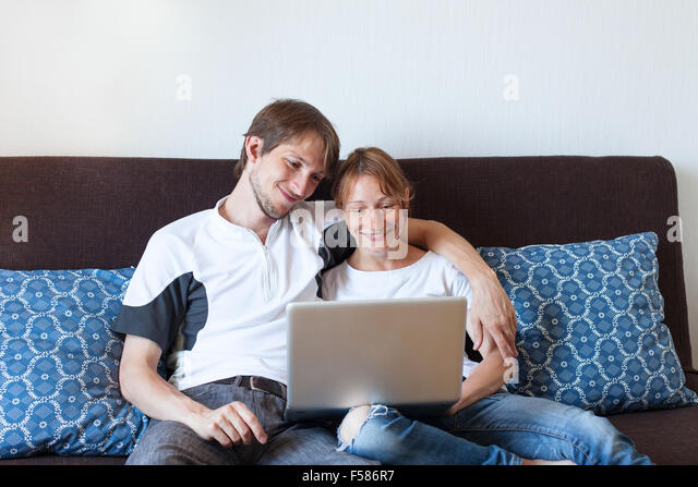 happy smiling couple with laptop at home, shopping online - Stock Image