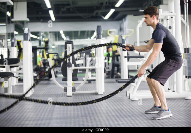 Young man exercising with battling rope at gym - Stock-Bilder